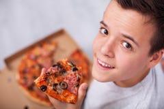 Glücklicher junger Jugendlichjunge, der eine Scheibe der Pizza - sitzend isst lizenzfreies stockfoto