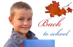 Glücklicher junger Junge mit den Büchern, die Kamera auf wh betrachten Lizenzfreies Stockbild