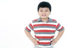 Glücklicher junger Junge mit den Händen auf seinen Hüften Lizenzfreies Stockbild