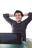 Glücklicher junger Kerl arbeitet an seinem Laptop Stockfotos