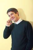 Glücklicher junger Kerl, der über Mobiltelefon spricht lizenzfreie stockbilder