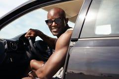 Glücklicher junger Kerl in seinem Auto Stockfotografie