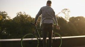 Glücklicher junger lächelnder Mann in der Sonnenbrille, die morgens einen Park oder einen Boulevard des Fahrrades radfährt Zeitlu stock video