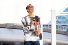 Glücklicher junger männlicher Student, der auf dem Campus mit intelligentem Telefon geht lizenzfreie stockfotografie
