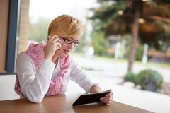 Glücklicher junger Manageranruf durch Smartphone im Restaurant lizenzfreies stockfoto