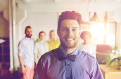Glücklicher junger Mann über kreativem Team im Büro Stockbilder