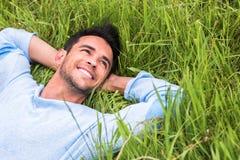 Glücklicher junger Mann auf dem grünen träumenden Gras und, dem Himmel oben betrachten relax lizenzfreies stockbild