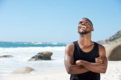 Glücklicher junger Mann, der über den Strand lacht Lizenzfreie Stockbilder