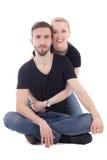 Glücklicher junger Mann, der auf dem Boden mit seinem Freundinisolat sitzt Stockbild