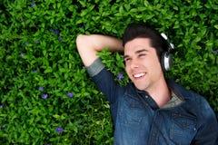 Glücklicher junger Mann, der auf dem Gras, hörend Musik liegt Stockfotografie