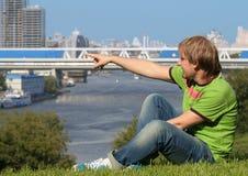Glücklicher junger Mann, der auf dem Gras sitzt Stockfoto