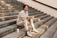 Glücklicher junger Mann, der auf den Schritten draußen schauen beiseite sitzt, halten Telefon lizenzfreie stockfotografie