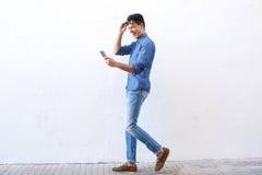Glücklicher junger Mann, der auf die Straße betrachtet Handy geht Lizenzfreie Stockbilder