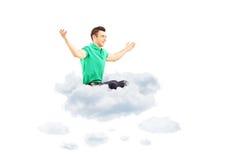 Glücklicher junger Mann, der auf einer Wolke sitzt und seine Arme verbreitet Stockbild