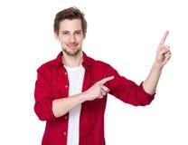 Glücklicher junger Mann, der auf Leerstelle auf dem Recht zeigt Stockfoto