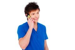Glücklicher junger Mann, der auf Mobiltelefon spricht Lizenzfreie Stockfotografie