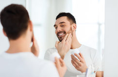 Glücklicher junger Mann, der Creme am Gesicht am Badezimmer aufträgt Stockfoto