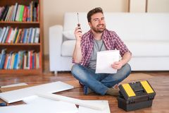 Glücklicher junger Mann, der die Anweisungen liest, Möbel zusammenzubauen stockbild