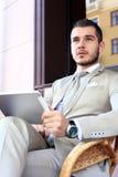 Glücklicher junger Mann, der digitale Tablette im Café verwendet Stockfotos