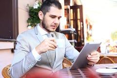 Glücklicher junger Mann, der digitale Tablette im Café verwendet Stockfoto