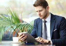 Glücklicher junger Mann, der digitale Tablette im Café verwendet Stockfotografie