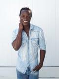 Glücklicher junger Mann, der draußen gegen weißen Hintergrund lächelt Stockbilder