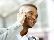 Glücklicher junger Mann, der durch Handy nennt Stockfotos
