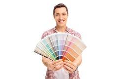 Glücklicher junger Mann, der ein Farbmuster hält Stockfoto