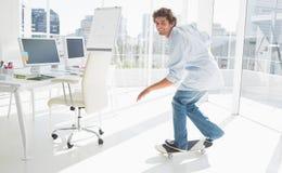 Glücklicher junger Mann, der in ein helles Büro Skateboard fährt Lizenzfreies Stockbild