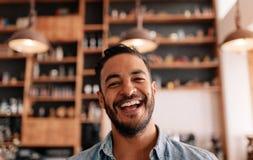 Glücklicher junger Mann, der in einem Café lacht lizenzfreie stockfotos