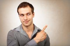 Glücklicher junger Mann, der Finger zeigt stockfoto