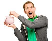 Glücklicher junger Mann, der Geld in das Sparschwein lokalisiert auf Weiß einsetzt Lizenzfreie Stockfotos