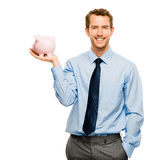 Glücklicher junger Mann, der Geld in das Sparschwein lokalisiert auf Weiß einsetzt Stockfotografie