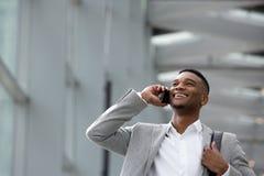 Glücklicher junger Mann, der am Handy innerhalb des Gebäudes spricht Stockfotografie