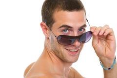 Glücklicher junger Mann, der heraus von den Sonnenbrillen schaut Stockfotos