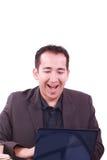 Glücklicher junger Mann, der an Laptop-Computer, habend arbeitet Stockbild