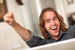 Glücklicher junger Mann, der Laptop-Computer verwendet Lizenzfreies Stockfoto