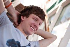 Glücklicher junger Mann, der mit den Händen auf seinem Kopf sich entspannt stockfotografie