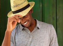 Glücklicher junger Mann, der mit Hut lacht und unten schaut Lizenzfreie Stockbilder