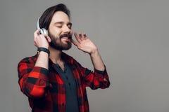 Glücklicher junger Mann, der Musik mit Kopfhörern hört stockfotografie