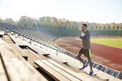 Glücklicher junger Mann, der oben auf Stadion läuft Stockfotografie