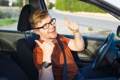 Glücklicher junger Mann, der oben im Auto und in den Showdaumen sitzt Stockfoto