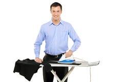 Glücklicher junger Mann, der seine Kleidung bügelt Stockbild
