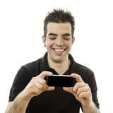Glücklicher junger Mann, der seinen Smartphone betrachtet Lizenzfreies Stockfoto