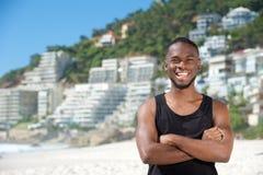 Glücklicher junger Mann, der am Strand lächelt Lizenzfreies Stockfoto