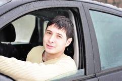 Glücklicher junger Mann, der von seinem Auto lächelt Lizenzfreie Stockfotos