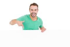 Glücklicher junger Mann, der weißes Brett zeigt Stockfoto