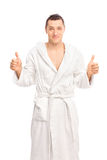 Glücklicher junger Mann in einem weißen Bademantel, der zwei Daumen lokalisieren gibt oben Lizenzfreies Stockfoto