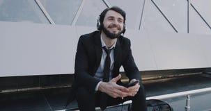 Glücklicher junger Mann in einer hörenden Überlegung der Klage unter Verwendung der Kopfhörer und im Sitzen neben der modernen Mi stock video footage