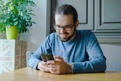 Glücklicher junger Mann im Café mit Smartphonegeschäftsbruch stockfotos